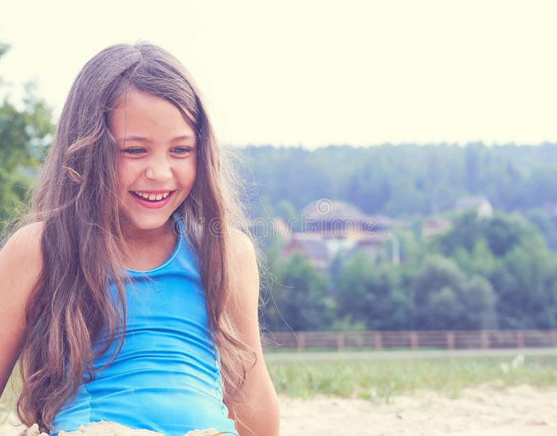 Cheerful happy little girl playing with send at beach enjoying nature - freedom concept. Resting outdoors enjoying sunny stock photo