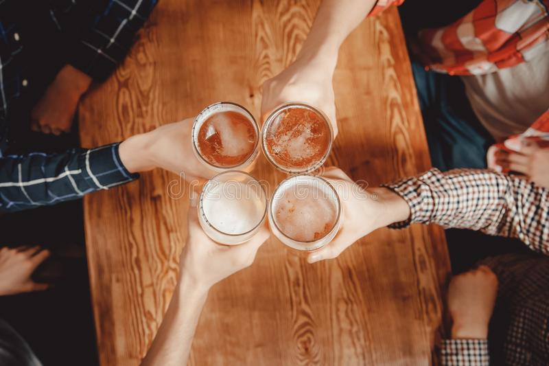 Cheerful and happy old friends are drinking draft beer at pub bar clink glasses. Top view. Friendship concept stock photos