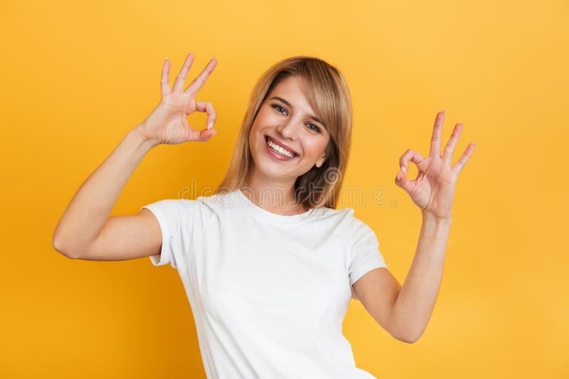 Cheerful happy pleased young pretty blonde woman posing isolated over yellow wall background dressed in white casual t-shirt. Image of a cheerful happy pleased stock image