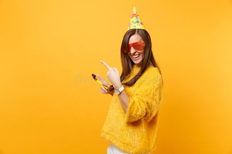 Cheerful happy woman in orange funny glasses, birthday hat with playing pipe pointing index fingers aside on copy space. Celebrating isolated on yellow stock photo