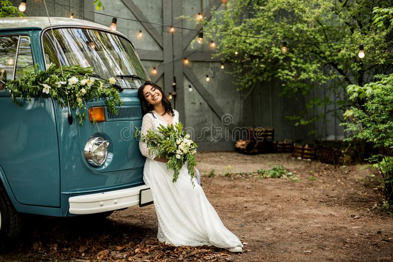 Cheerful happy young bride sit on the bumper retro-minibus. Close-up. stock image