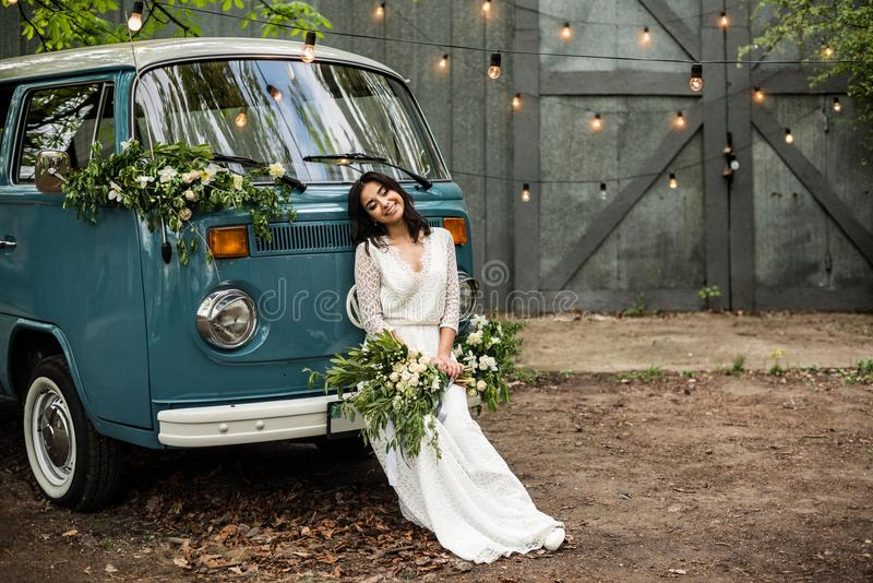 Cheerful happy young bride sit on the bumper retro-minibus. Close-up. stock photography
