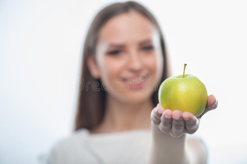 Cheerful healthy woman is holding green apple royalty free stock photography