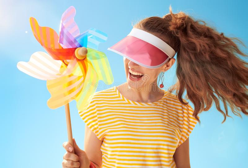 Woman hiding behind sun visor holding colorful windmill. Cheerful healthy woman in yellow shirt against blue sky hiding behind sun visor holding colorful royalty free stock photo
