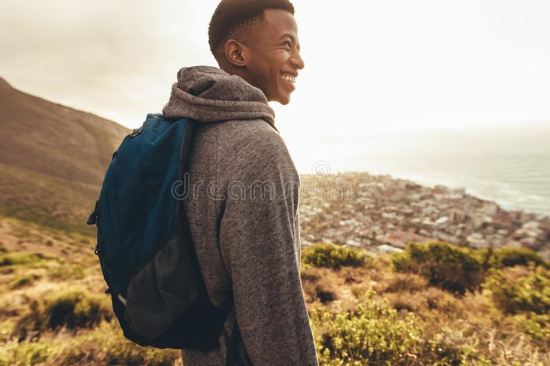 Cheerful hiker admiring the view. Cheerful african man with backpack standing on mountain trail and looking away. Young guy on hiking trip looking happy stock photo