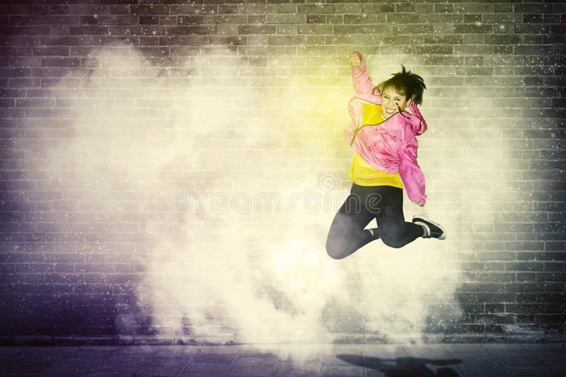 Cheerful hip-hop dancer jumping with smoke. Cheerful hip-hop dancer jumping and dancing with smoke in brick wall background royalty free stock photography