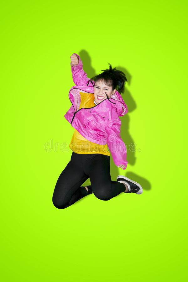 Cheerful hip-hop dancer jumping on studio. Cheerful hip-hop dancer jumping and dancing in the studio with green screen background royalty free stock photography