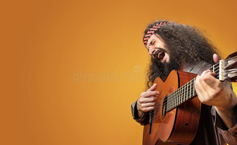 Cheerful hippe playing a guitar stock photography