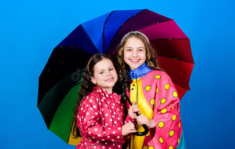 Cheerful hipster children, sisterhood. autumn fashion. happy little girls with colorful umbrella. rain protection. Rainbow. family bonds. Little girls in royalty free stock images