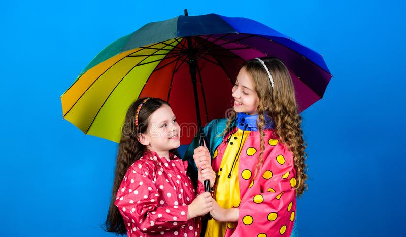 Cheerful hipster children, sisterhood. rain protection. Rainbow. happy little girls with colorful umbrella. family bonds. Little girls in raincoat. autumn royalty free stock photography