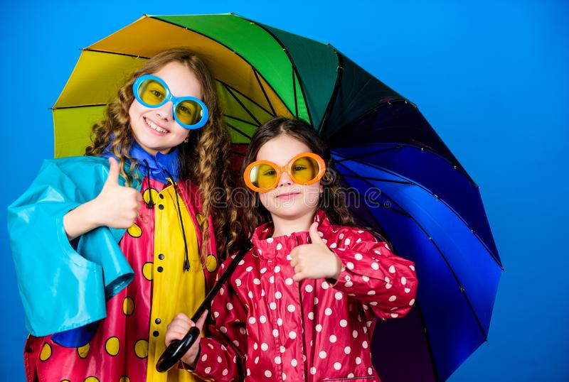 Cheerful hipster children, sisterhood. rain protection. Rainbow. happy small girls with colorful umbrella. family bonds. Small girls in raincoat. autumn royalty free stock photo