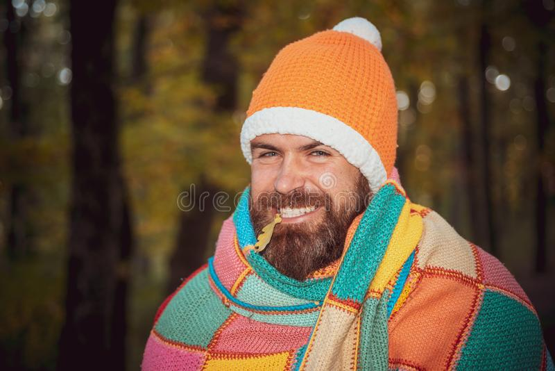 Cheerful hipster man with beard wrapped in a multicolor blanket, wearing warm hat, smiling on the camera. Concept of. Resistance to seasonal diseases, colds stock photography