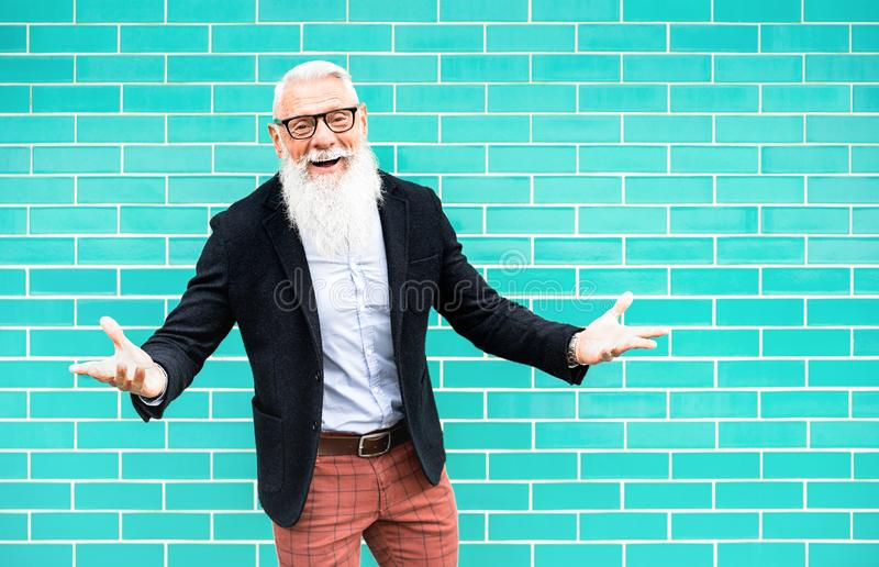 Cheerful hipster man on welcome mood posing against turquoise wall background - Trendy old person wearing casual fashion clothes. Happy elderly lifestyle royalty free stock image