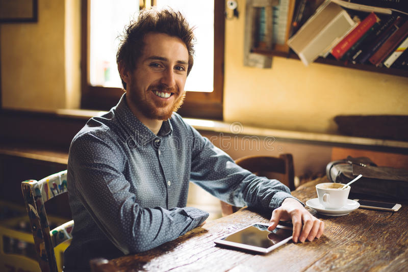Cheerful hipster social networking with his tablet royalty free stock image