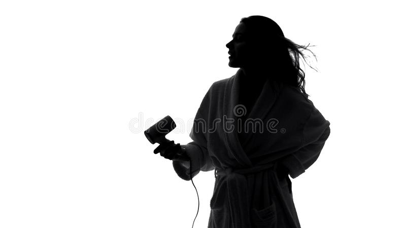 Cheerful housewife blow drying hair and imagining herself popular singer, shadow stock images