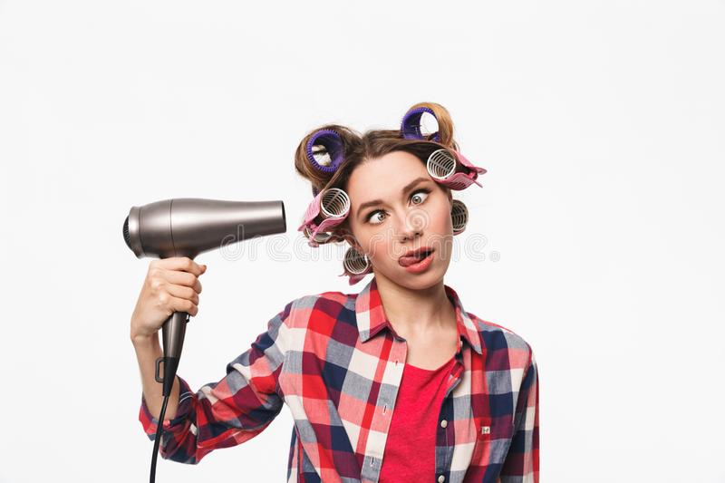 Cheerful housewife with curlers in hair standing stock images
