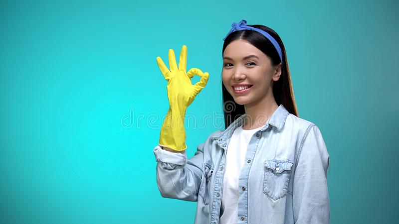 Cheerful housewife in gloves showing ok gesture at camera, house cleaning royalty free stock images