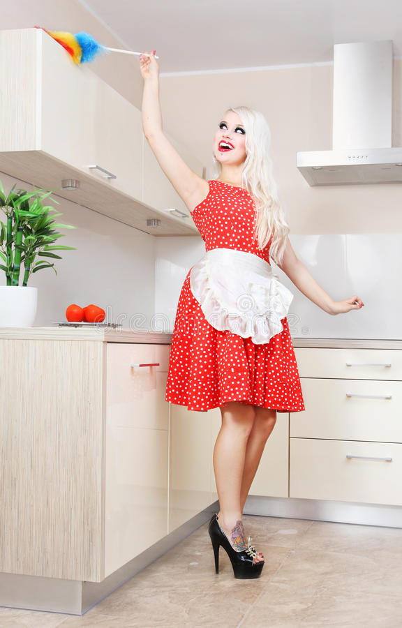 Cheerful housewife in the kitchen stock photography