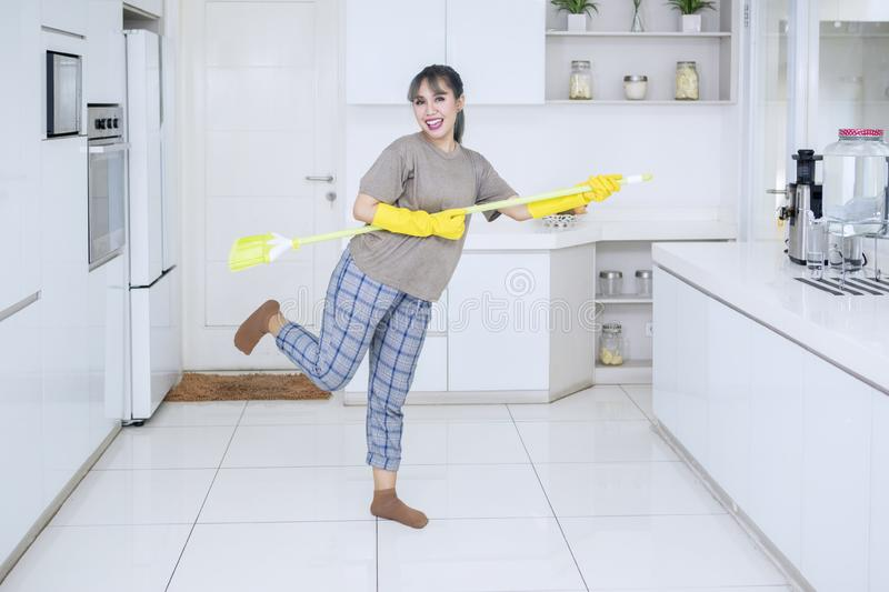 Cheerful housewife playing guitar with a broom royalty free stock photos