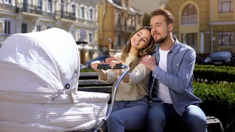 Cheerful husband wife hugging swinging newborn in stroller, parenthood happiness. Stock photo stock photos