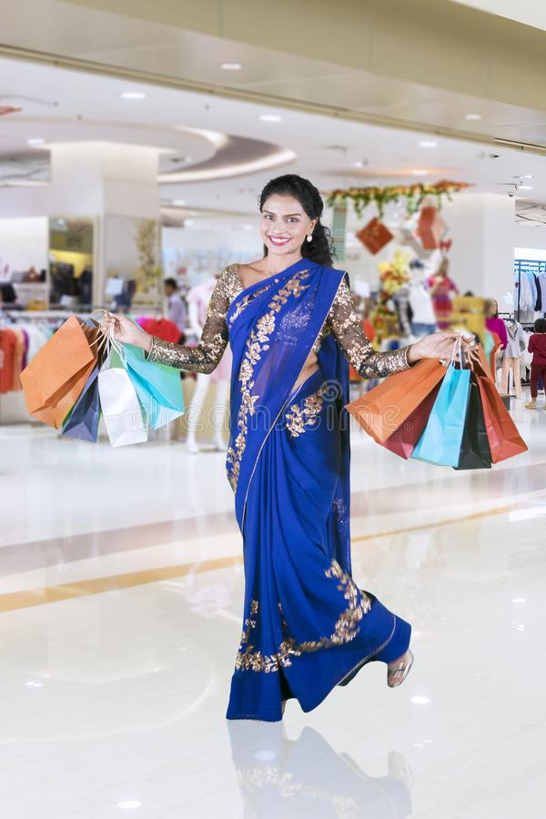 Cheerful Indian woman with shopping bags at mall stock photos