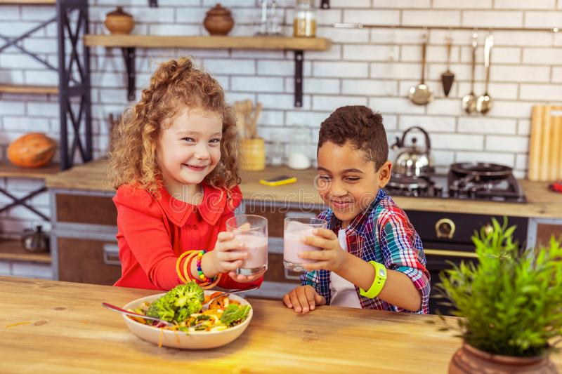 Cheerful international kids posing on camera in kitchen. Favorite drink. Cute girl expressing positivity while sitting near her cousin royalty free stock images