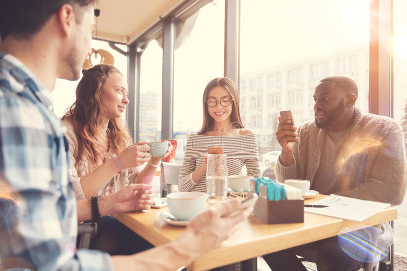 Cheerful international students resting in the cafe royalty free stock image
