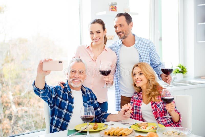 Cheerful, joyful relatives, stylish company, festive couples having fun in house, room, apartment, handsome senior with grey hair stock photography