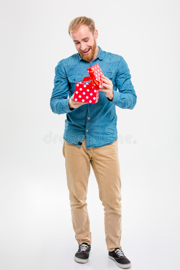 Cheerful joyful young blond bearded man opening gift. Full length portrait of cheerful joyful young blond bearded man opening gift over white background royalty free stock photo