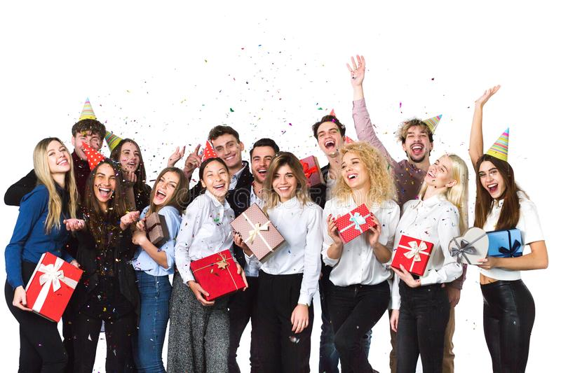 Cheerful joyful young people friends standing and celebrating together over white background. royalty free stock images