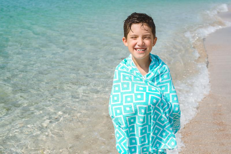 A cheerful kid on the beach wrapped in a bright beach towel. stock photography