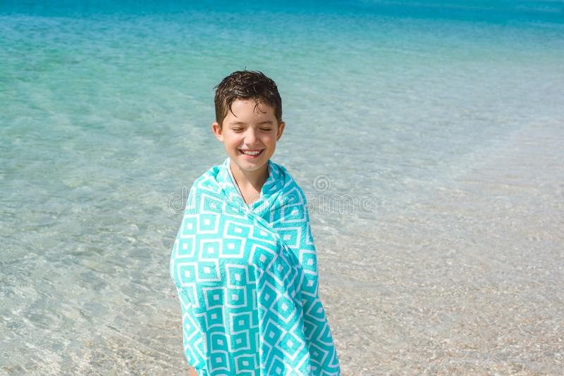 A cheerful kid on the beach wrapped in a bright beach towel. stock photos