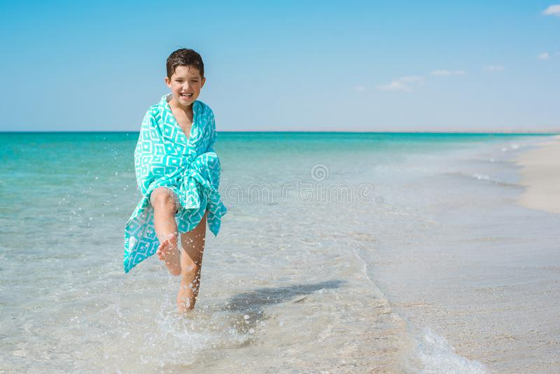 A cheerful kid on the beach wrapped in a bright beach towel. stock photo