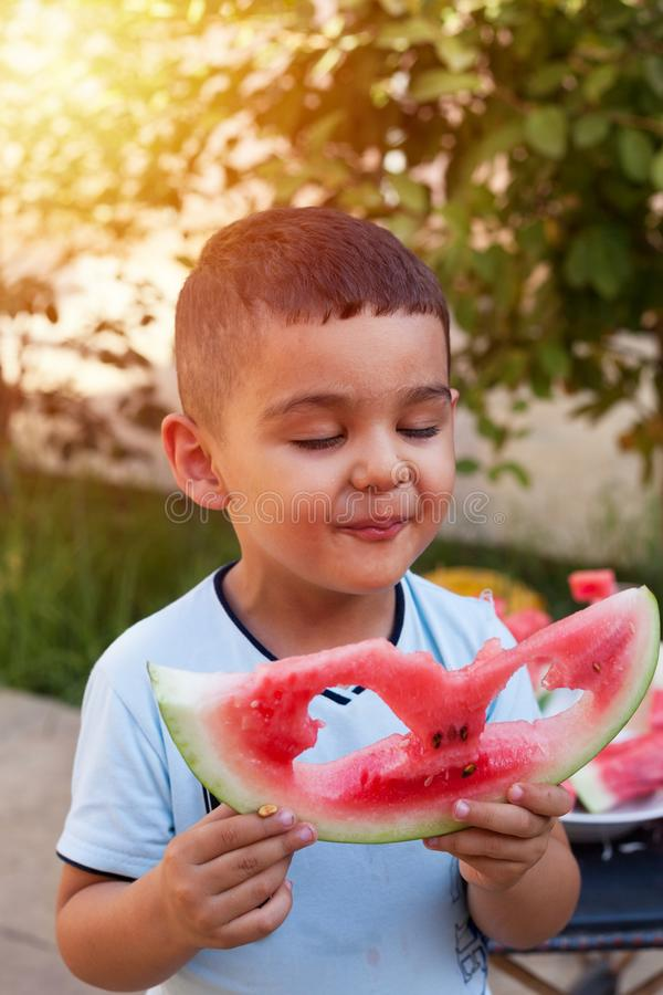 Cheerful kid boy eating a watermelon slice with two heart shape holes stock image