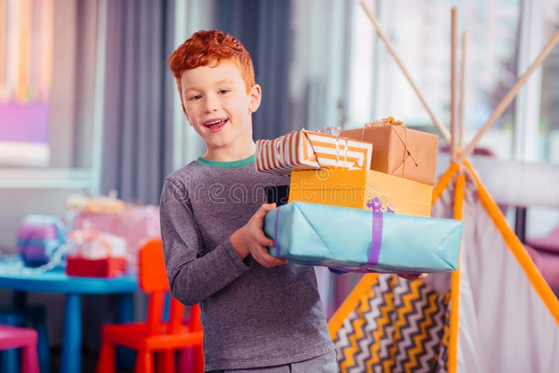 Cheerful kid demonstrating his colorful gift boxes. It is mine. Pleased red-haired boy expressing positivity while having birthday party stock images