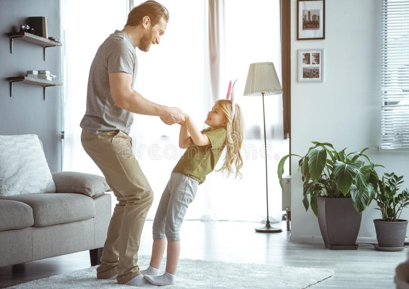 Cheerful kid having fun with dad in apartment stock photo