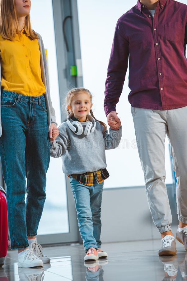 Cheerful kid holding hands of father and mother stock photography