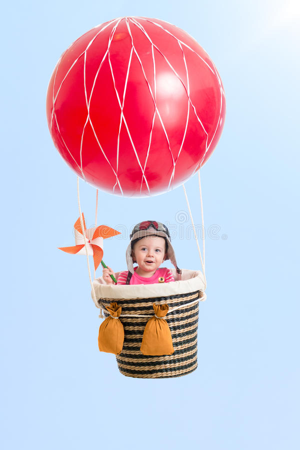 Cheerful kid on hot air balloon in the sky. Cheerful kid girl on hot air balloon in the sky royalty free stock image