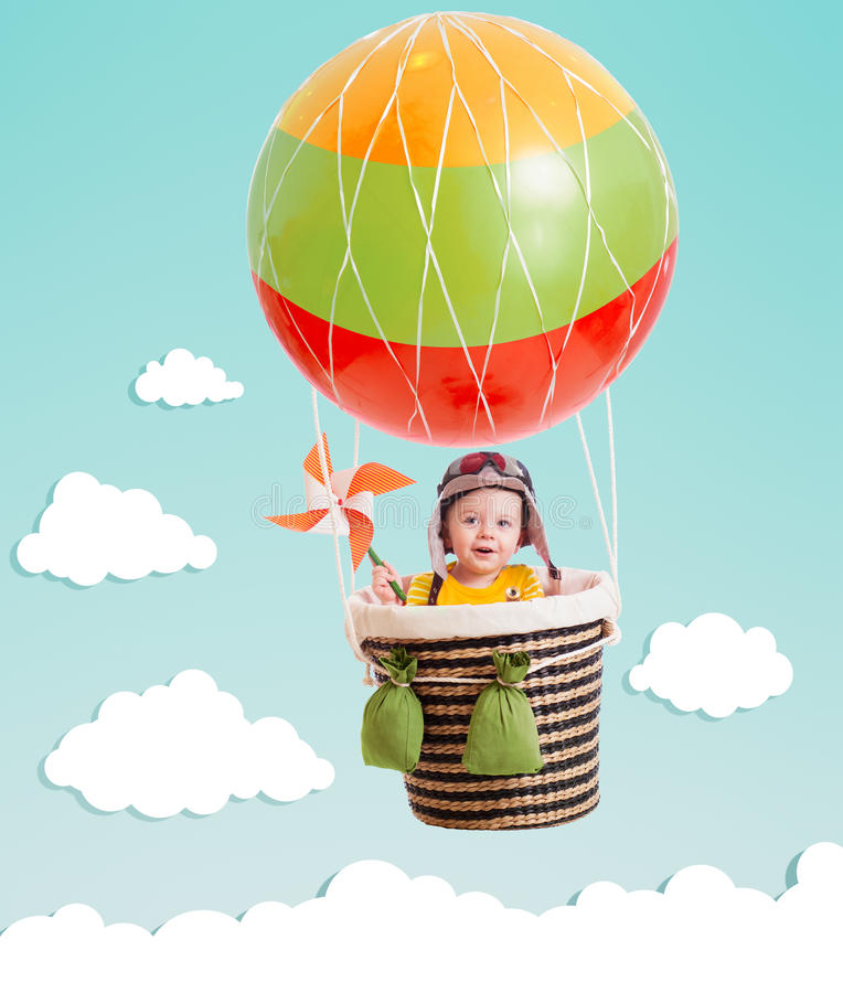Cheerful kid on hot air balloon in the sky. Cheerful kid girl on hot air balloon in the sky stock image