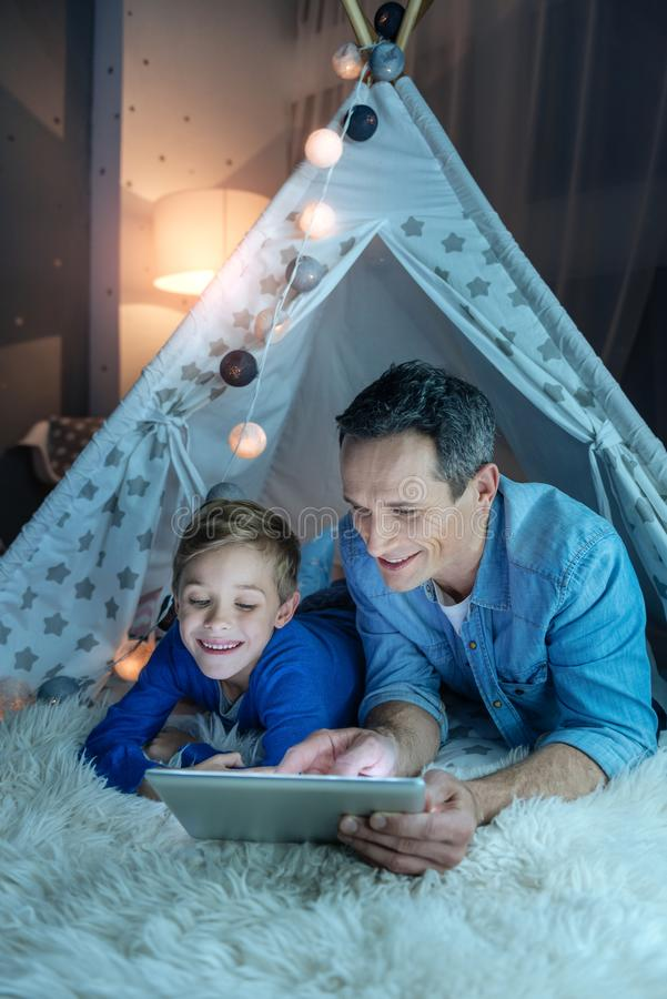 Cheerful kid looking at screen of tablet royalty free stock image