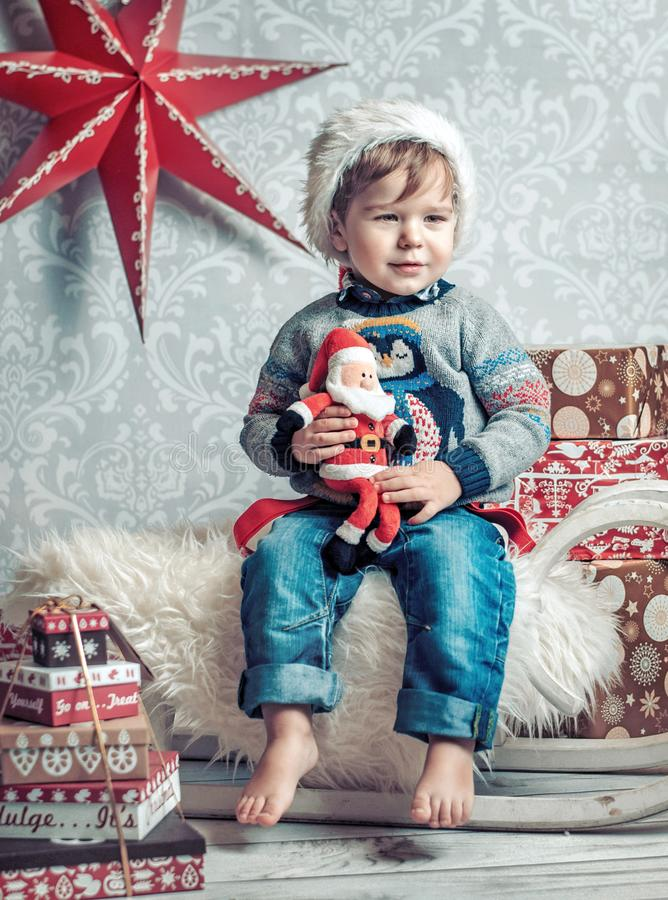 Cheerful kid sitting on a christmas sleigh royalty free stock photos