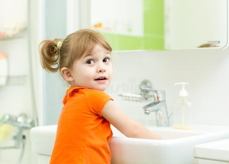 Kid washing hands and showing soapy palms stock photo