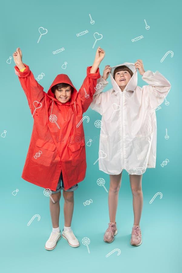 Cheerful kids feeling happy while wearing their new beautiful rain coats stock photo