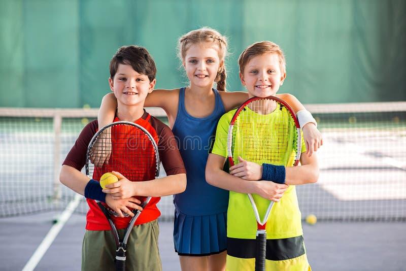 Cheerful kids having fun on tennis court stock photos