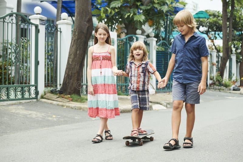 Children teaching boy skateboarding royalty free stock images