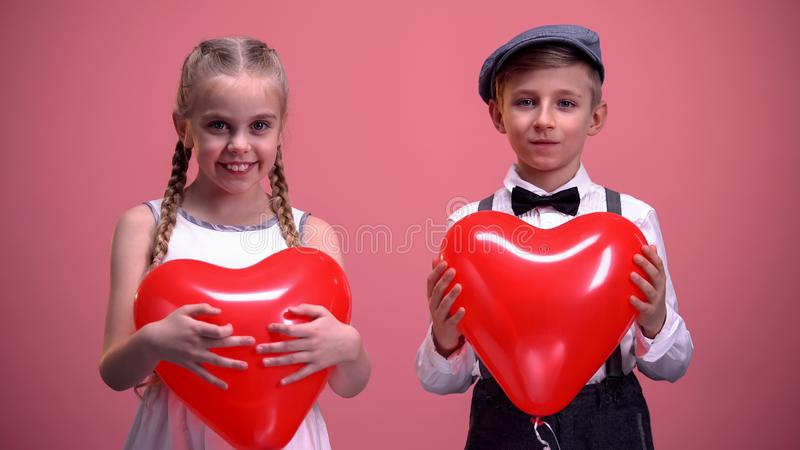 Cheerful kids in love holding red heart-shaped balloons and smiling to camera stock images