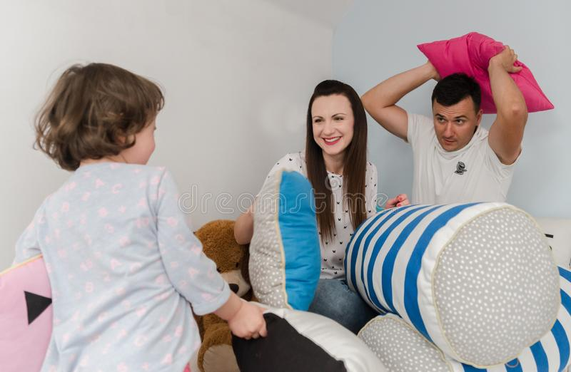 Cheerful kids and parents having pillow fight on bed at home stock images