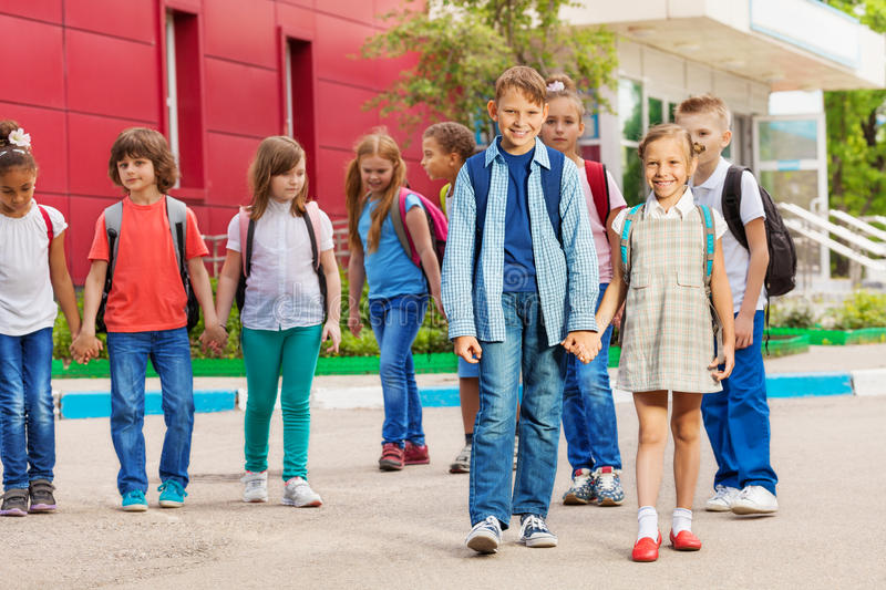 Cheerful kids with rucksacks near school building. Walking holding hands during summer day time royalty free stock photos