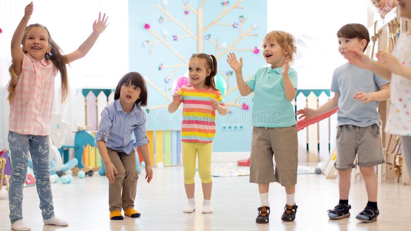 Cheerful kids stand semicircle on floor in kindergarten or day care centre. Preschoolers have fun indoors, playing games stock photo