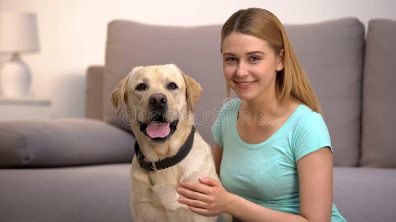 Cheerful labrador retriever dog female owner smiling to camera pet companionship. Stock photo royalty free stock photo